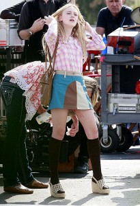 Dakota Fanning holds still while an assistant cleans up her menstrual blood.