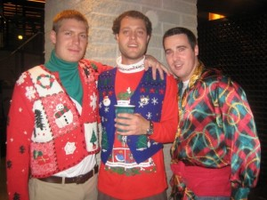 Three unidentified men wearing hideous Christmas sweaters.