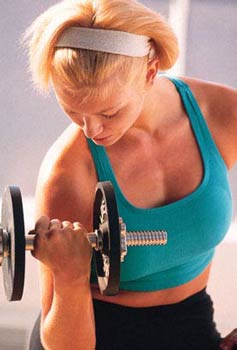 Image of slender white woman doing bicep curls with small barbell.